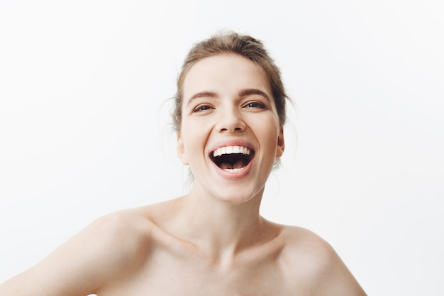 Close up of joyful beautiful young caucasian woman with dark long hair in bun hairstyle, being half naked, laughing with delight and happy face expression. beauty and health.