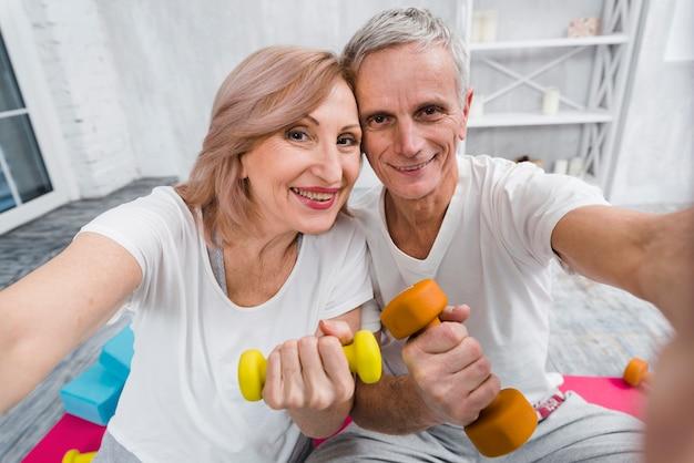 Close-up of joyful loving senior couple exercising with dumbbells