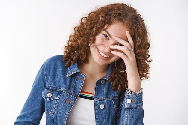 クローズアップうれしそうなポジティブな笑顔の魅力的な若い赤毛の女性そばかすのにきびが頭を傾けて笑うのんきな赤面顔を隠すニヤリと面白い話の冗談を聞く、白い背景に立っている