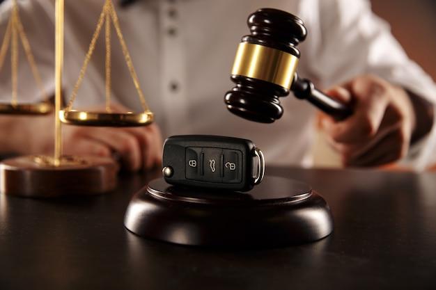 Close up of judge gavel and car keys over soundboard on white background