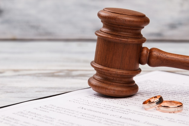 Close-up judge gavel and wedding rings.