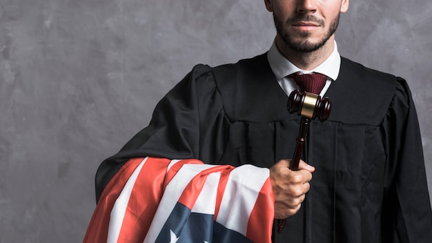 Close-up  judge in robe holding gavel and flag