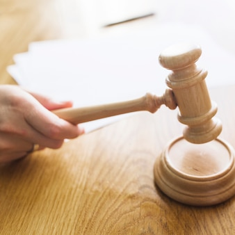 Close-up of a judge's hand striking gavel on sounding block