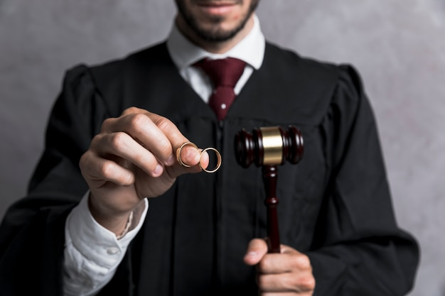 Close-up judge with golden rings and gavel