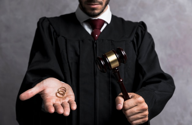 Close-up judge with wedding rings and gavel