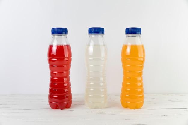 Chiuda sulle bottiglie del succo sulla tavola con fondo bianco