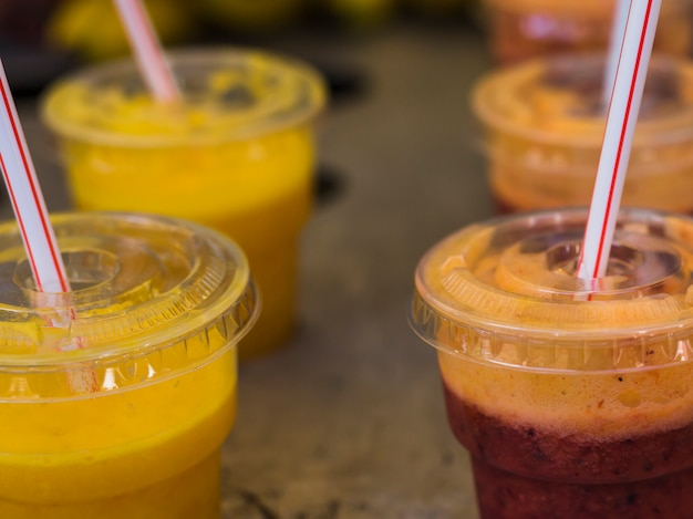 Close-up of juice in disposable plastic cup with straws