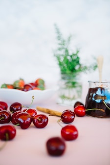 Close-up of juicy cherries with jam on desk