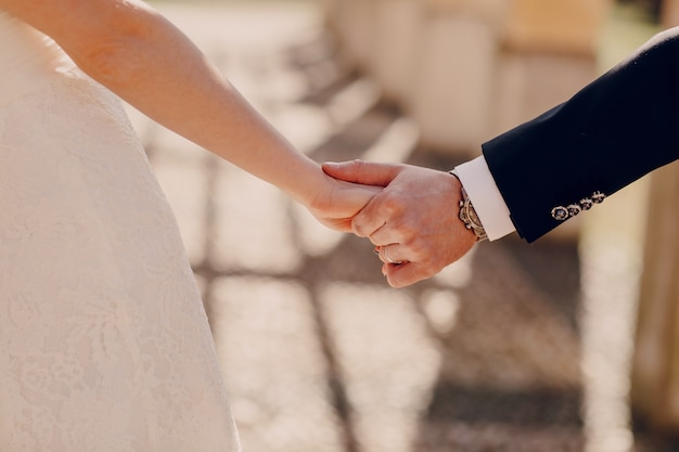 Close-up of just-married couple holding hands