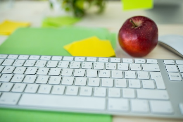 Close-up of a keyboard with apple on desk