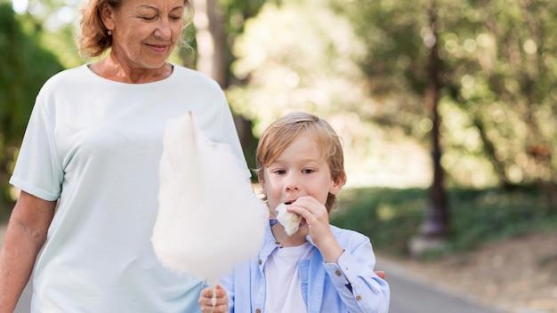 Крупным планом ребенок и бабушка с сахарной ватой