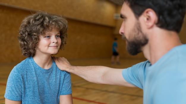 Крупным планом ребенок и учитель спорта