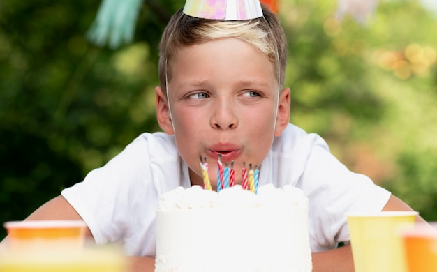 Close up kid blowing out candles