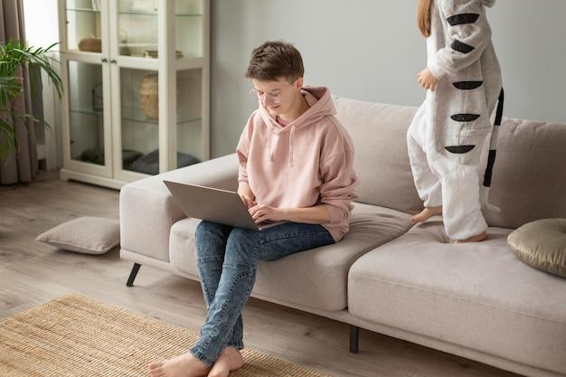 Chiuda sul bambino sul divano e sui genitori che lavorano