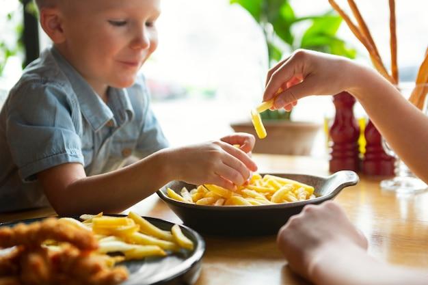 Chiuda sul bambino che mangia patatine fritte