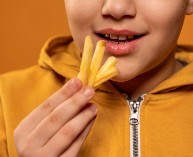 Bambino del primo piano che mangia patatine fritte