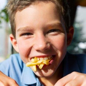 フライドポテトを食べる子供をクローズアップ