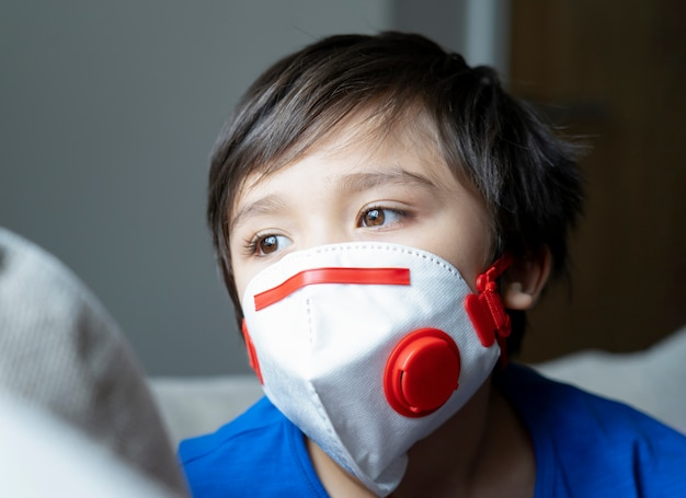 Close up kid face looking  tired from chest coughing wearing face mask for protect pm2.5, child boy  with sad face stay at home for protection form coronavirus