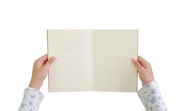 Закройте вверх руки ребенка, держа и откройте книгу с пустой страницей на белом фоне с обтравочным контуром