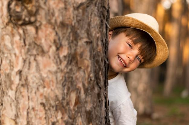 Close-up kid hiding behind tree