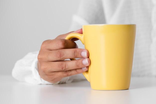 Малыш крупным планом держит желтую чашку
