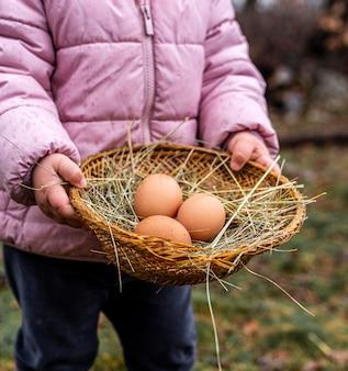 Крупным планом ребенок держит корзину с яйцами