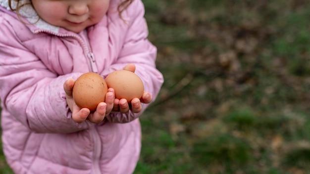 Крупным планом ребенок держит яйца