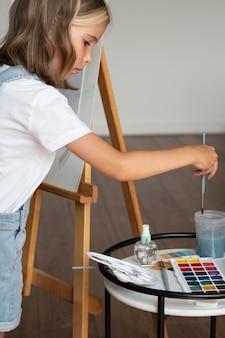 Крупным планом ребенок держит кисть для рисования