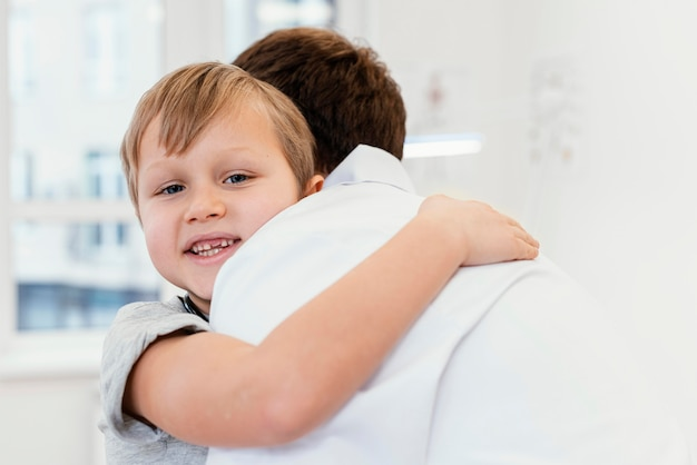 医者を抱き締めるクローズアップの子供