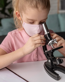 Close up kid learning with microscope