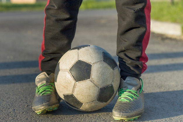 Close-up of kid legs in sportive footwear holding soccer ball outdoors on sunny day. teenager vacations activity, sport training and recreation concept.