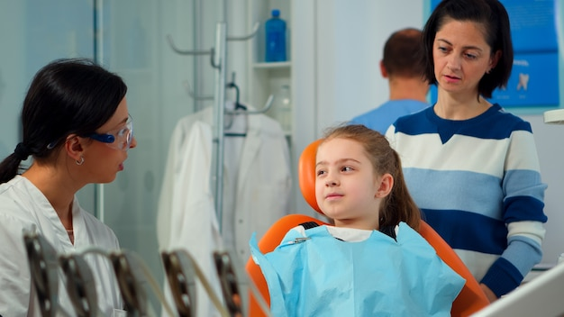 Close up of kid patient with toothache wearing dental bib talking with dentist before intervetion showing to affected mass. girl sitting on stomatological chair while nurse preparing sterilized tools.