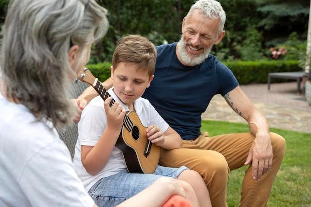 조부모를 위해 음악을 연주하는 아이를 닫습니다