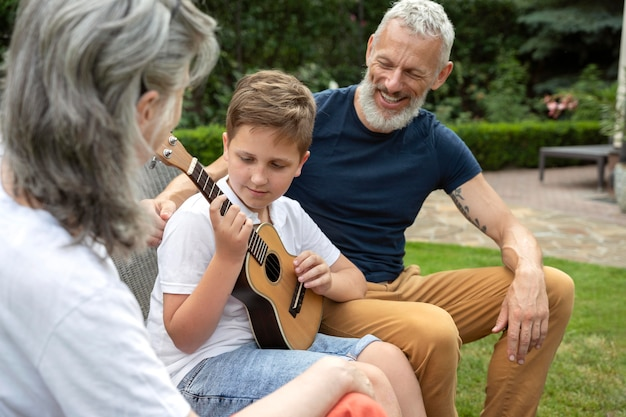 Close up kid playing music for grandparents