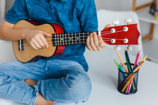 근접 아이가 책상에 앉아 소프라노 우쿨렐레를 연주. 레저에서 기타를 배우는 유치원 소년. 유아 교육 및 음악 취미의 개념