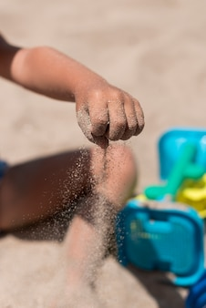Close up of kid pouring sand