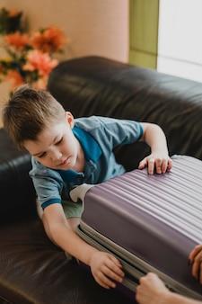 Bambino del primo piano che prepara i bagagli