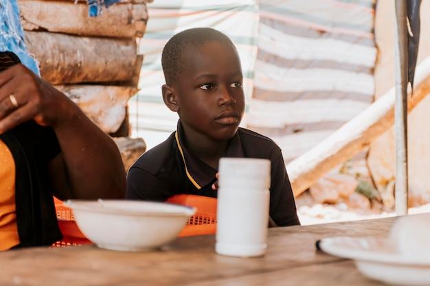 Bambino del primo piano che si siede al tavolo