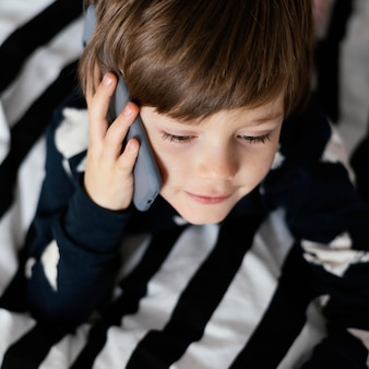 Close-up kid talking on phone