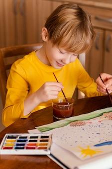 Bambino del primo piano usando gli acquerelli