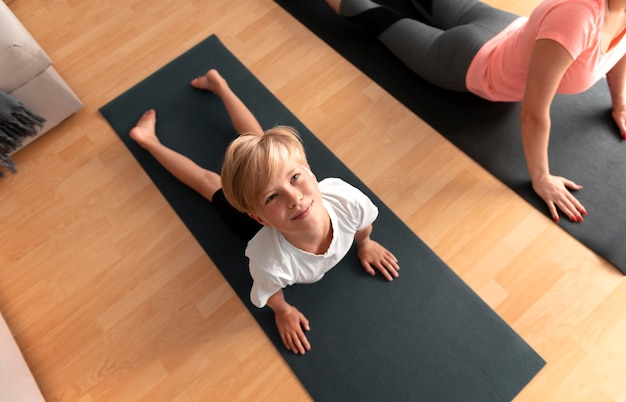 Close up kid and woman with yoga mats