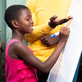 Close-up kid writing on board