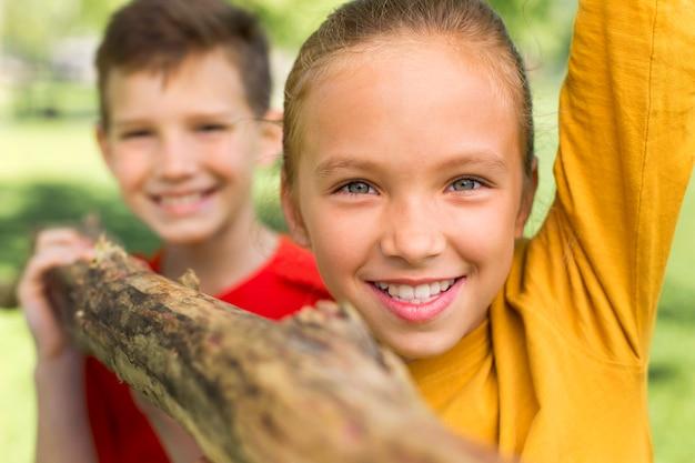 Close up kids carrying log as team