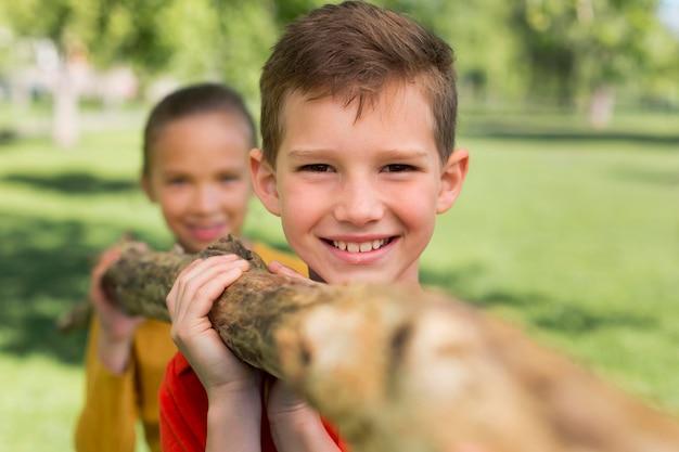 Close up bambini che trasportano log