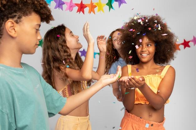 Bambini ravvicinati che festeggiano con i coriandoli