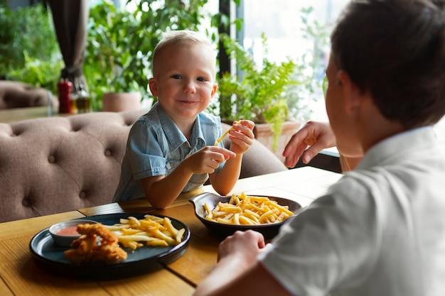 Chiudere i bambini che mangiano fast food