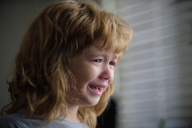 Close up of a kids face crying tears. upset child. violence in family over children. concept of bullying, depressive stress or frustration.