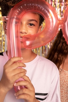 Close up kids holding balloons