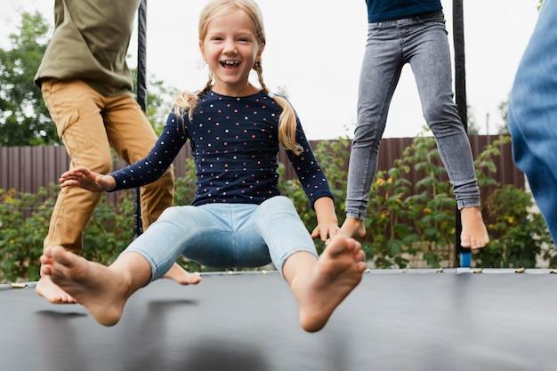 Крупным планом дети прыгают на батуте