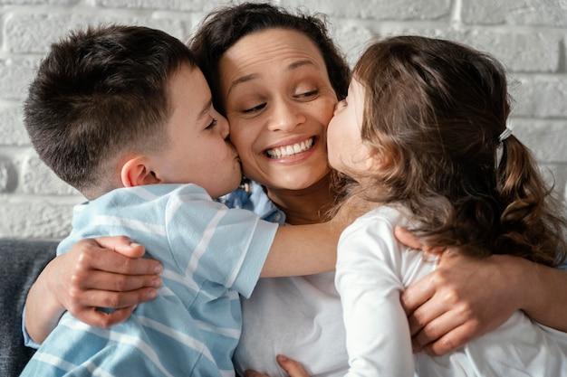 母親にキスする子供たちをクローズアップ
